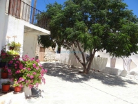 The traditional square Mpechraki in Kastro, Chora with flowers, trees and spreaded clothes