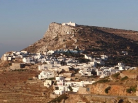 The sun sets over the houses of Kastro and the monastery of Zoodochou Pigis in Sikinos